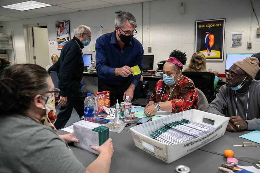 Lansing city clerk Chris Swope instructs election workers as they sort absentee ballots to count at the Lansing city clerk's office on election night, on Nov 3, 2020.