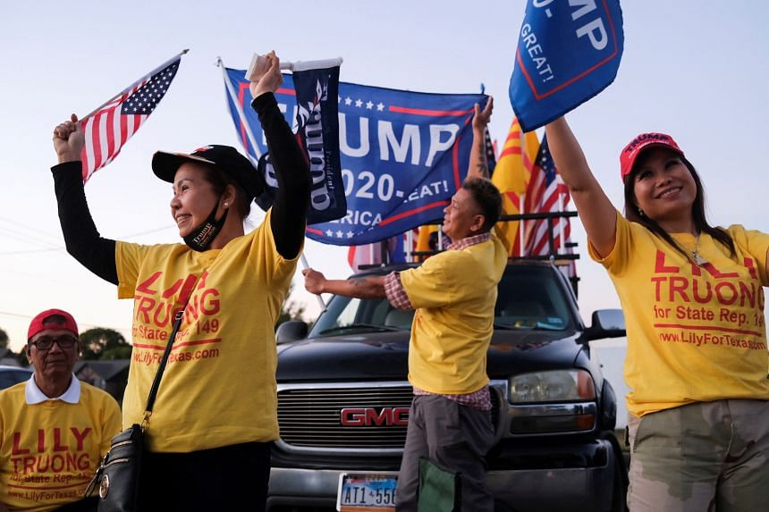 Trump supporters wave flags outside a polling site, on Election Day in Houston, Texas, US, on Nov 3, 2020.