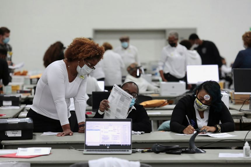 Poll workers tabulate absentee ballots at Detroit, Michigan, on Nov 3, 2020.