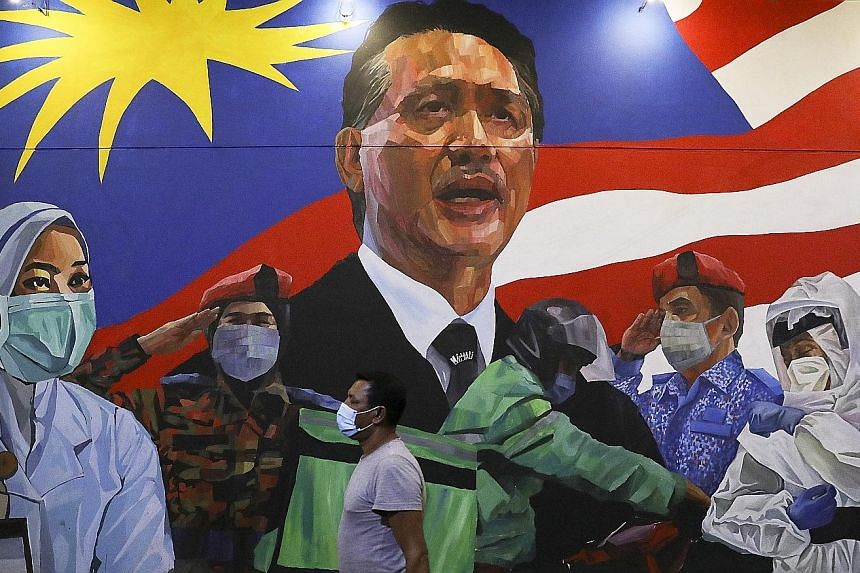 A mural tribute to frontline workers in the fight against the coronavirus pandemic, in Damansara in Kuala Lumpur. The Malaysian capital is under a conditional movement control order which bans inter-district travel, has shut schools and restricts sho