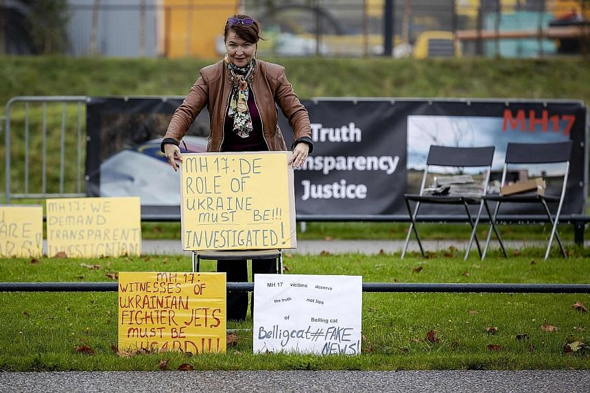 A pro-Russian protester holding a placard outside Schiphol Judicial Complex, in the Netherlands, where the trial on the 2014 downing of the Malaysia Airlines jet continues. All 298 people on board were killed.