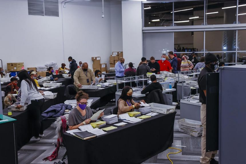 Absentee ballots are processed and verified by the Fulton County Registration and Elections Department in a large room at State Farm Arena in Atlanta, Georgia, on Nov 4, 2020.