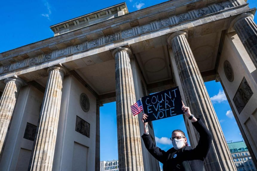 """A member of the """"Democrats Abroad"""" organisation demonstrates near the US embassy in Berlin on Nov 4, 2020."""