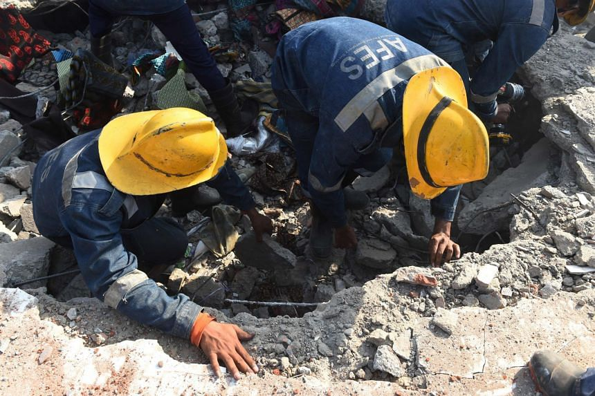 Emergency services search for survivors in the debris of a collapsed garment warehouse after the blast.