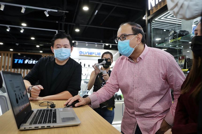 Communications and Information Minister S Iswaran looking at T K Foto's online website with managing director James Ng on Nov 6, 2020.