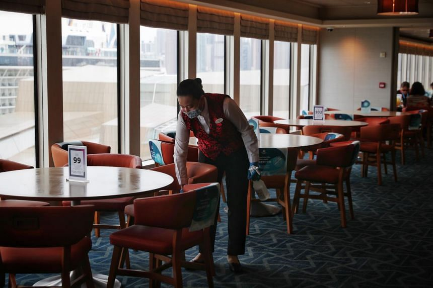 A staff member cleaning at a restaurant onboard the World Dream cruise ship on Nov 6, 2020.