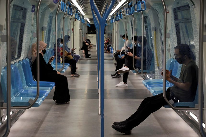 Commuters wearing masks and following safe-distancing measures taking a ride on board a Mass Rapid Transit train in Kuala Lumpur, on Oct 30, 2020.