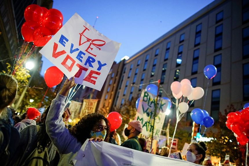 People gather with signs as votes continue to be counted, in Philadelphia, Pennsylvania, on Nov 5, 2020.