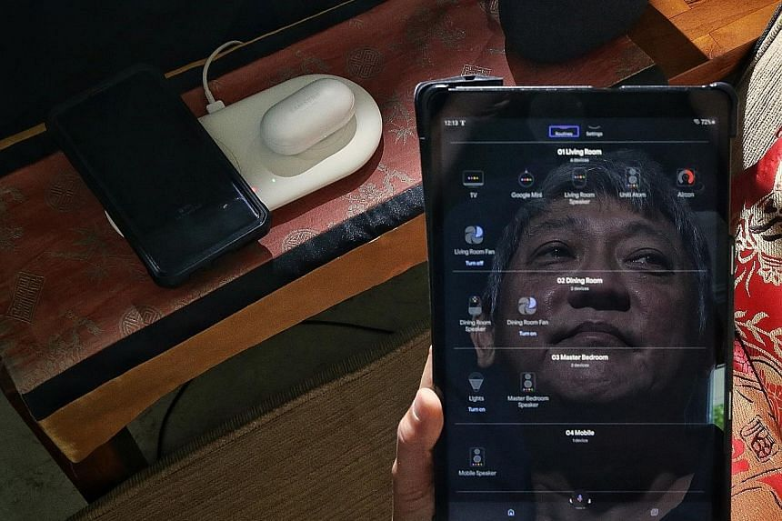 Mr Dennis Teo, who is almost completely blind, says technology helps him in various ways. A reflection of his face is seen above on the screen of a smart device that lets him control his home appliances using his voice.