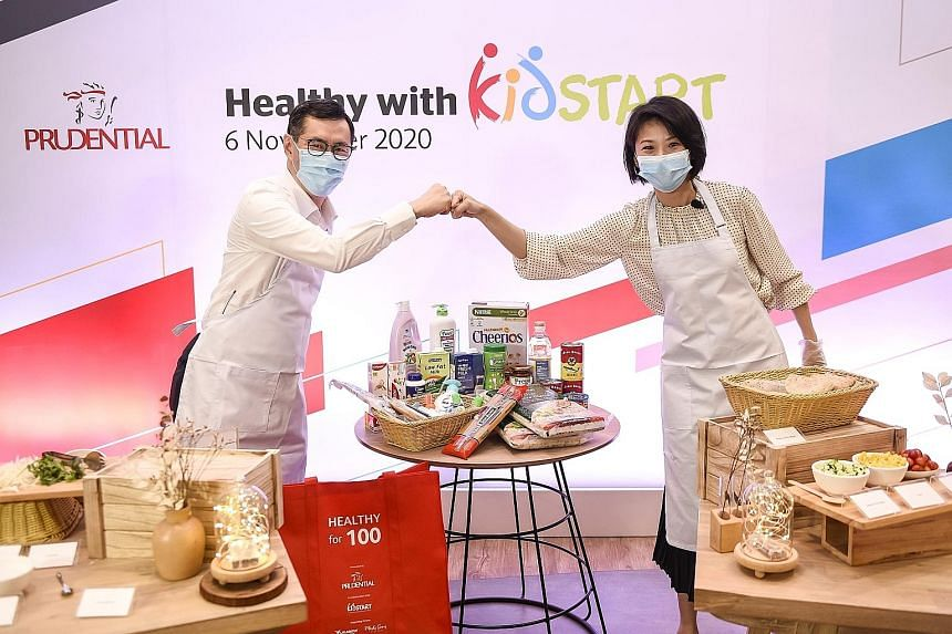 Minister of State for Social and Family Development and Education Sun Xueling and Prudential Singapore's chief executive Dennis Tan taking part in a cook-off session at the launch of the Healthy with KidStart programme yesterday. PHOTO: PRUDENTIAL SI