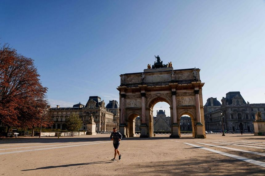 A jogger runs in front of Arc de Triomphe in Paris on Nov 6, 2020, during a Covid-19 lockdown.