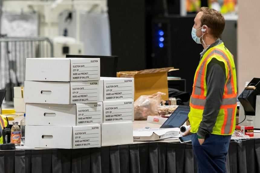 An electoral worker stands next to boxes with ballot material in Philadelphia on Nov 6, 2020.