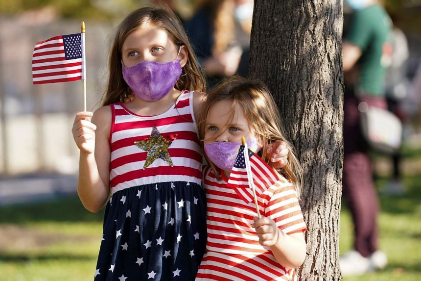 Girls hold American flags as Biden supporters celebrate in Wilmington, Delaware.