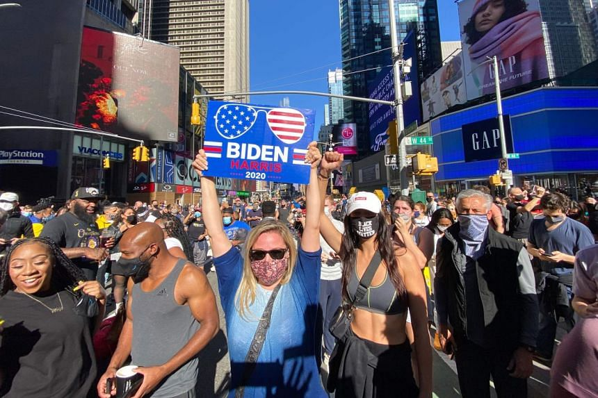 People celebrate at Times Square in New York after Joe Biden was declared the election winner.