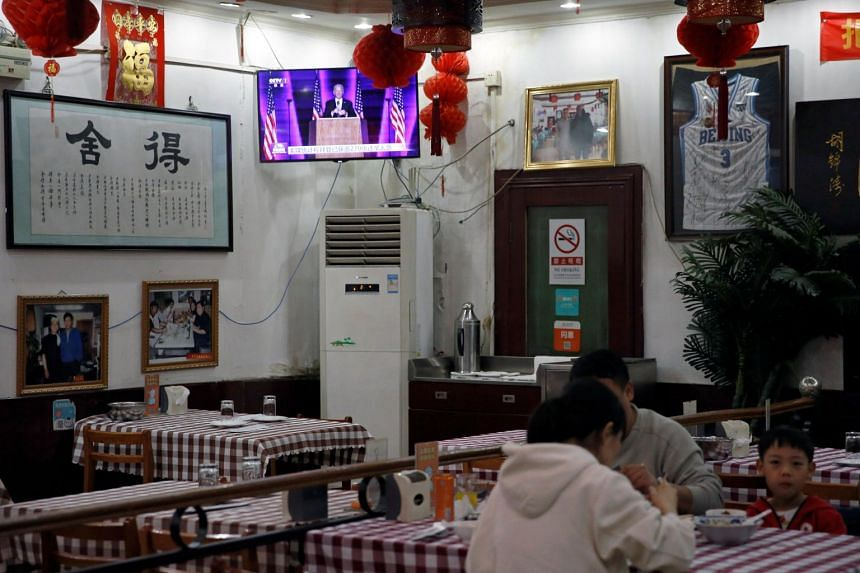 A screen shows a news report of US President-elect Joe Biden delivering a speech, in a restaurant in Beijing on Nov 8, 2020.