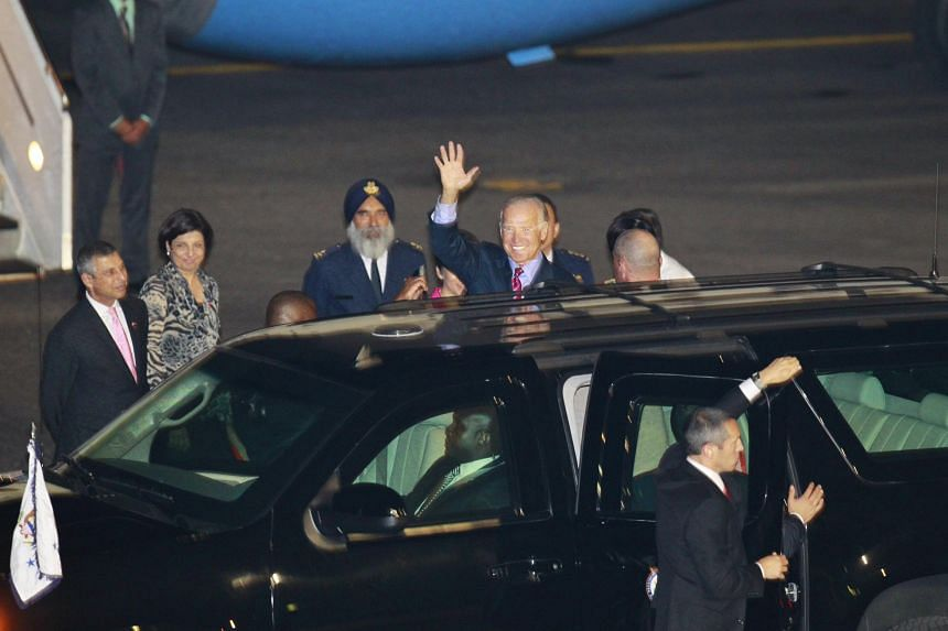 Joe Biden waves to the media after he arrives with his wife Jill at Paya Lebar Airbase on July 25, 2013.