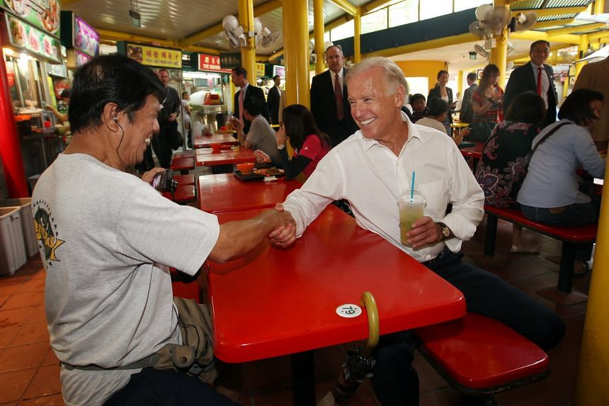 Joe Biden greets a patron during a surprise visit to the Adam Road hawker centre on July 26, 2013.