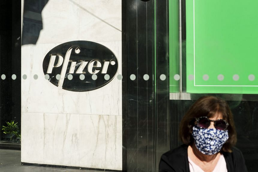 A woman walks past the Pfizer headquarters in New York, on Nov 9, 2020.