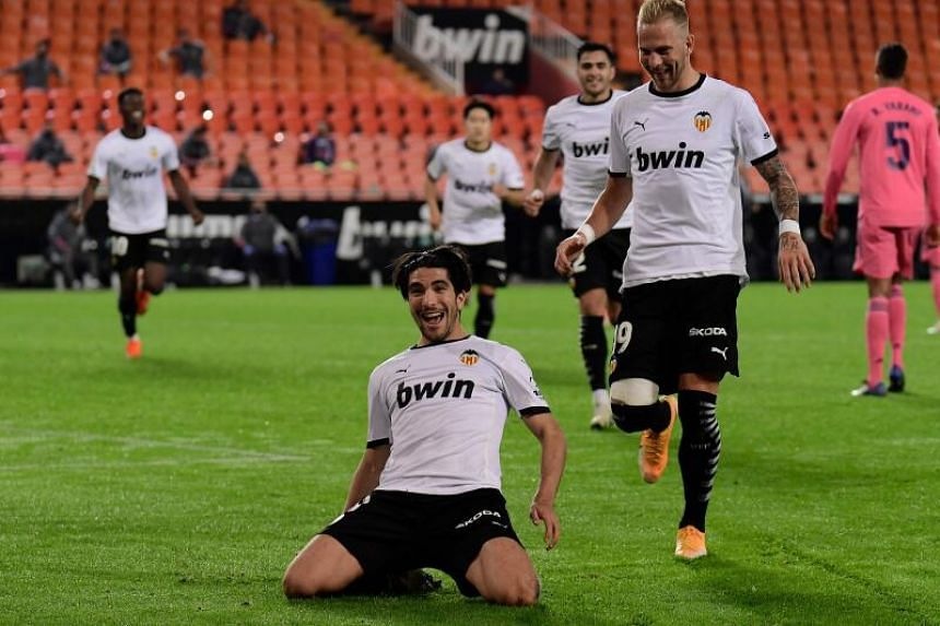 Valencia midfielder Carlos Soler (kneeling) celebrates after scoring a goal in their 4-1 win over Real Madrid at the Mestalla stadium on Sunday as Uros Racic joins in.