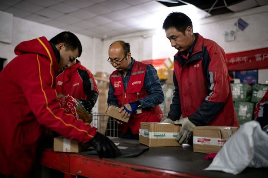 Delivery workers handle packages at a warehouse in Beijing on Nov 9, 2020, to be delivered to customers ahead of the Singles' Day.