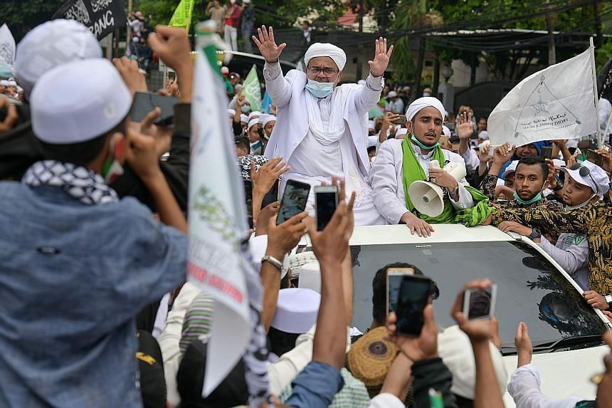 Rizieq Shihab (centre), leader of the hardline Islamic Defenders Front, greeting supporters at their headquarters in Jakarta yesterday, following his return from Saudi Arabia.