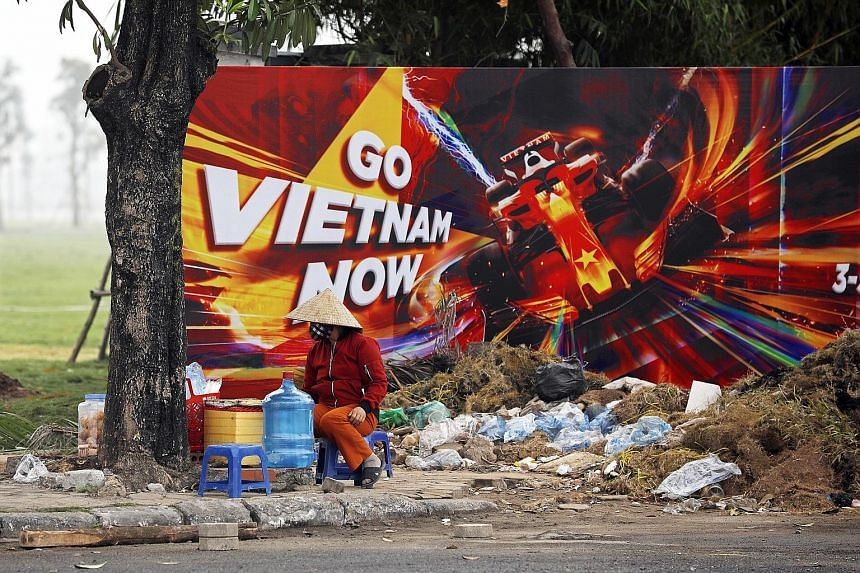 A street vendor sitting in front of a poster promoting the Vietnamese Grand Prix at the construction site of the Hanoi Street Circuit in March. The race will not be on the calendar for next year, while F1 did not give a reason for its omission.
