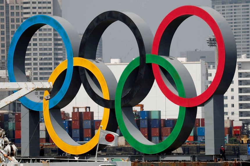 The giant Olympic rings are seen behind Japan's national flag in Tokyo.
