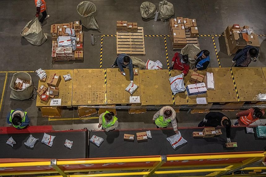Workers sorting packages at an automated logistics centre for Chinese e-commerce giant