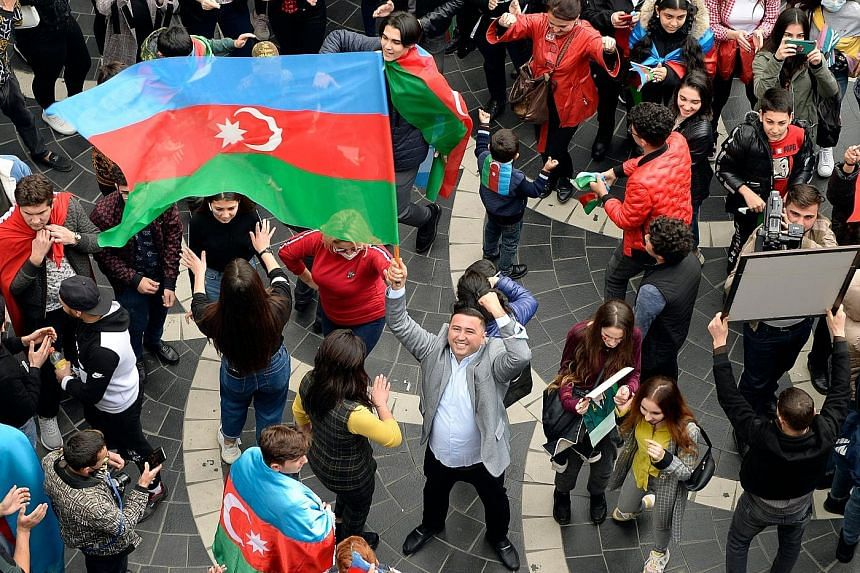 Azerbaijanis celebrating in the streets of the capital Baku on Tuesday after the peace deal was reached. The country reclaimed 15 per cent to 20 per cent of its lost territory during the recent conflict. PHOTO: AGENCE FRANCE-PRESSE