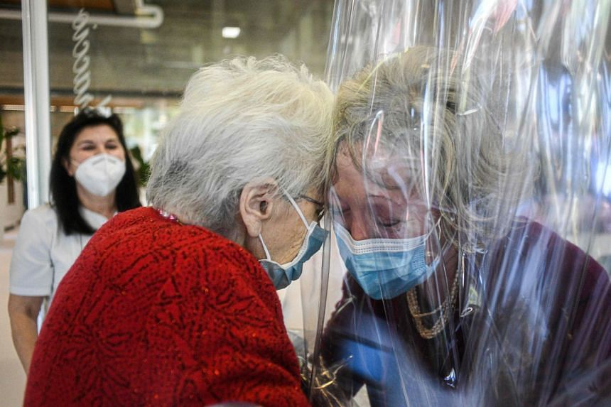 A resident (left) of a nursing home near Venice hugs her visiting daughter on Nov 11, 2020.