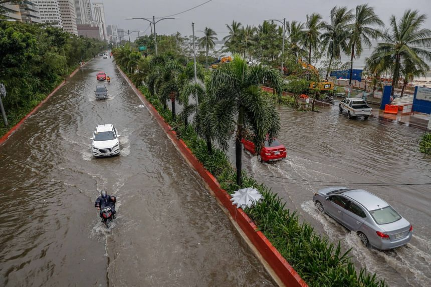 Motorists drive along a flooded road in Manila on Nov 12, 2020.