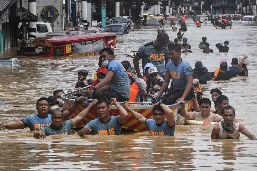 Rescuers pull a rubber boat carrying residents through a flooded street in Marikina City, Manila, on Nov 12, 2020.