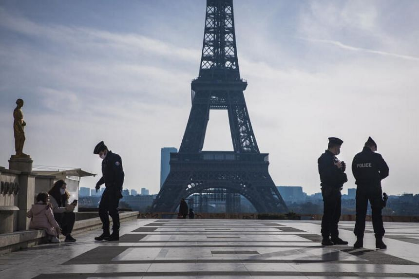 French police officers patrol in the deserted Trocadero square near the Eiffel Tower in Paris on Nov 7, 2020.