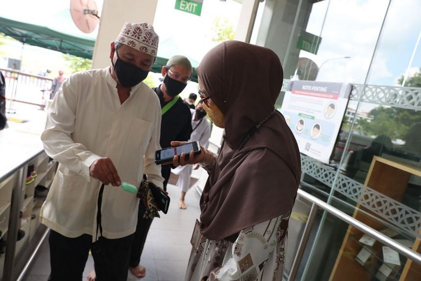 Congregants checking in using the TraceTogether token at Masjid Maarof at Jurong West St 26.
