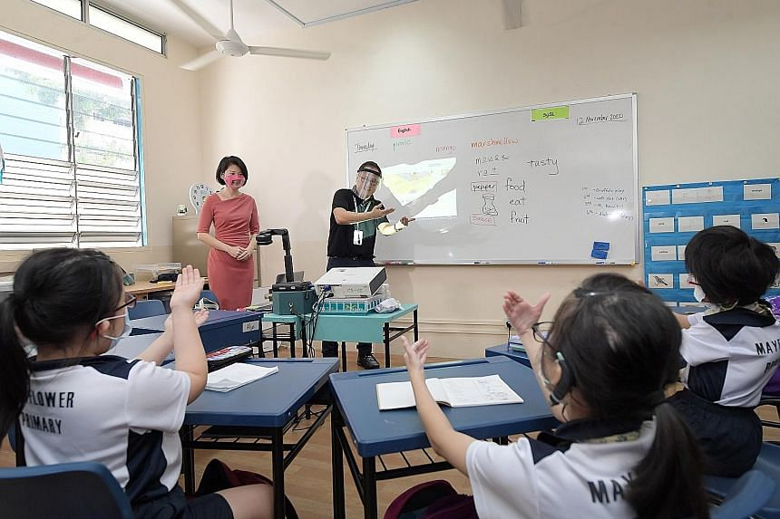 Minister of State for Education Sun Xueling watching as specialised teacher David Lee conducted a class yesterday at Mayflower Primary School. Besides having a dedicated sign language teacher, children will have access to external speech and language