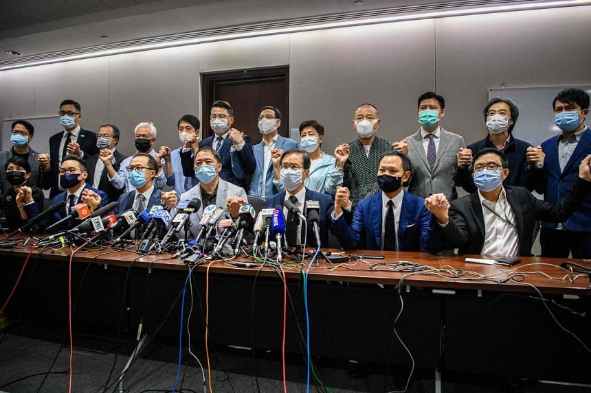 Pro-democracy lawmakers join hands at the start of a press conference in Hong Kong on Nov 11, 2020.