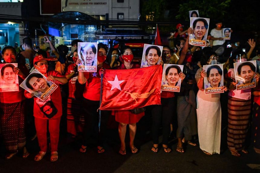 Supporters of the National League for Democracy party hold portraits of Aung San Suu Kyi as they celebrate in front of the party's headquarters in Yangon.