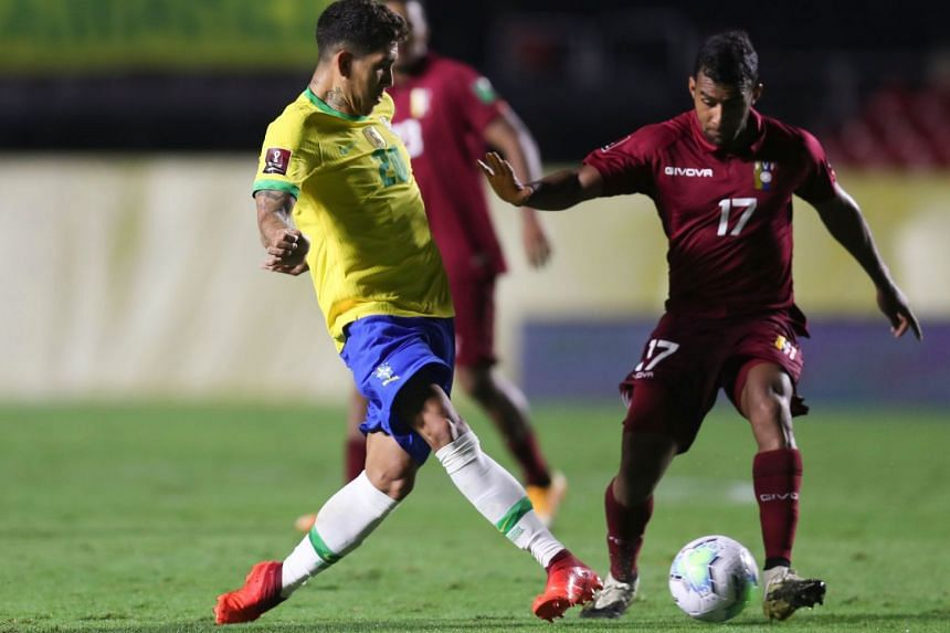 Brazil's Roberto Firmino and Venezuela's Cristian Casseres vie for the ball in the World Cup South American qualifier at Morumbi Stadium in Sao Paulo on Nov 13, 2020.