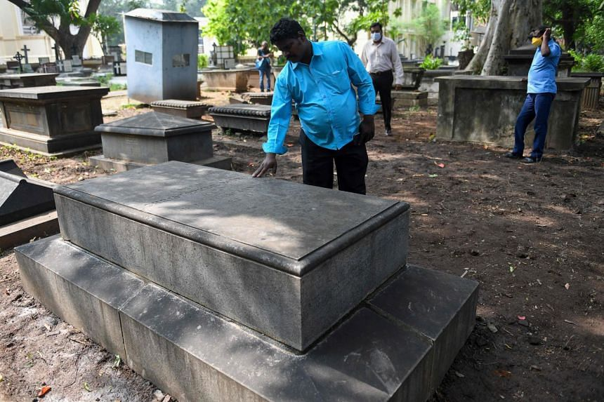 A St George's Cathedral worker shows the grave of Christoper Biden, a potential ancestor of US President-elect Joe Biden, in Chennai.