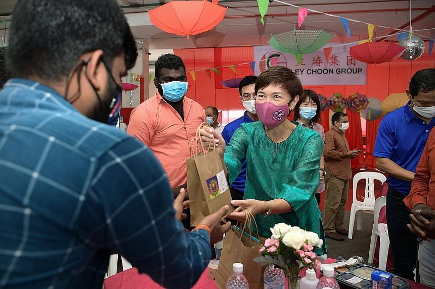 Manpower Minister Josephine Teo distributing goodie bags to migrant workers at a factory-converted dorm in Sungei Kadut yesterday. ST PHOTO: NG SOR LUAN