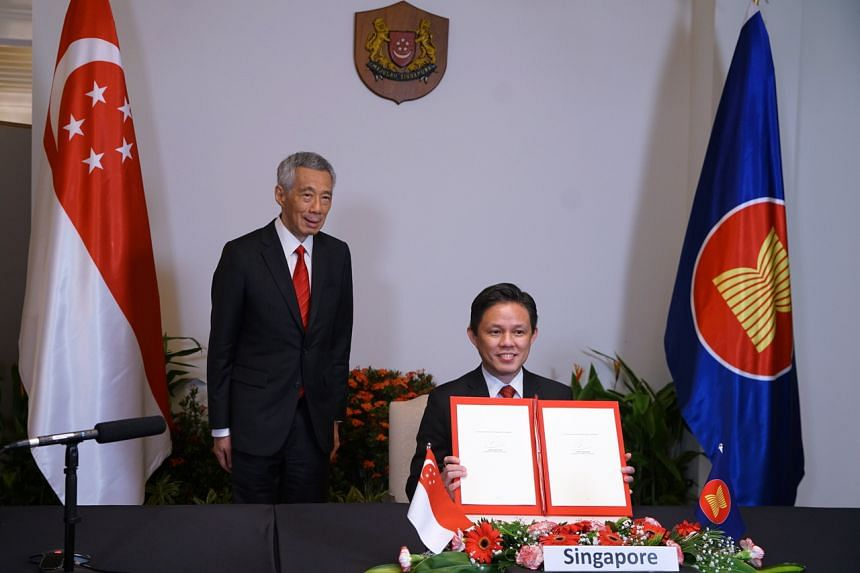 Trade and Industry Minister Chan Chun Sing (right), together with PM Lee Hsien Loong, showing off the document after the RCEP signing ceremony on Nov 15, 2020.