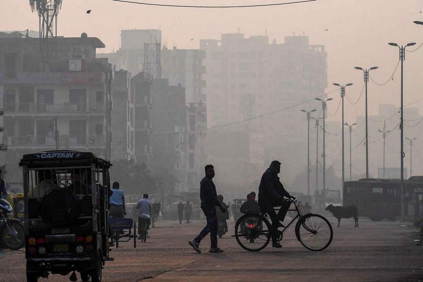 People make their way along a street amid smoggy conditions in New Delhi on Nov 15, 2020.