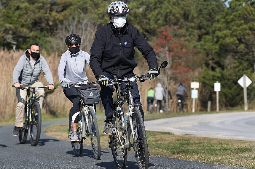 US President-elect Joe Biden and his wife, Jill Biden, cycling in Cape Henlopen State Park, Delaware, last Saturday. Observers expect Washington under Mr Biden to re-engage with the international community, and to resume discussions on some issues bl