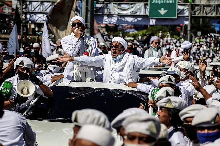 Radical Indonesian cleric Habib Rizieq Shihab gesturing to supporters as he arrived to inaugurate a mosque in Bogor city last Friday. With Indonesia entering its first recession since 1998 due to the coronavirus pandemic, Rizieq is well placed to con