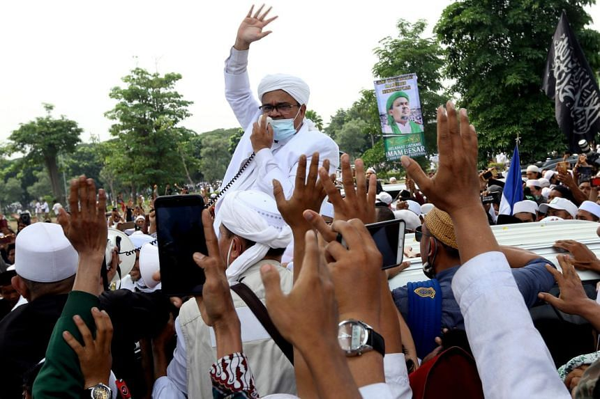Indonesia's radical cleric Rizieq Shihab greets people as he arrives at Soekarno-Hatta International Airport on Nov 10.