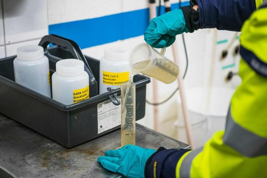 A researcher pours a sample of wastewater into a small container in Stockholm, Oct 21, 2020. Researchers have been testing wastewater from three facilities since mid-April after studies showed that remnants of the novel coronavirus could be detected