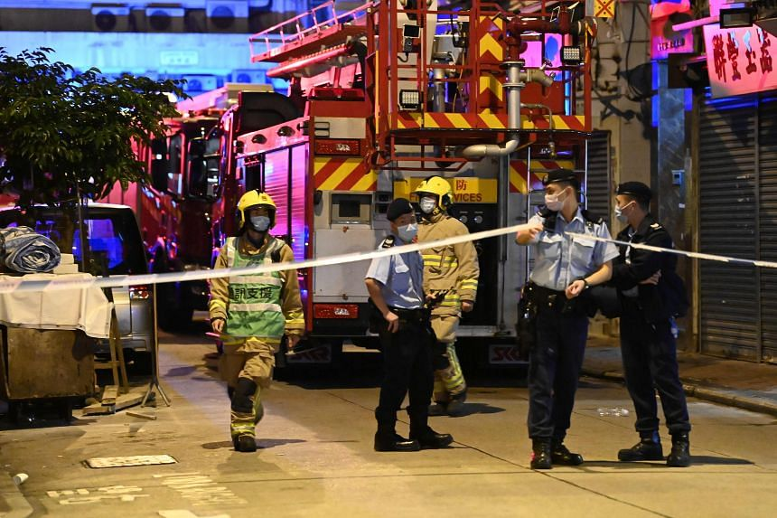 Police officers and firemen work at the location of a fire in Hong Kong on Nov 16, 2020.