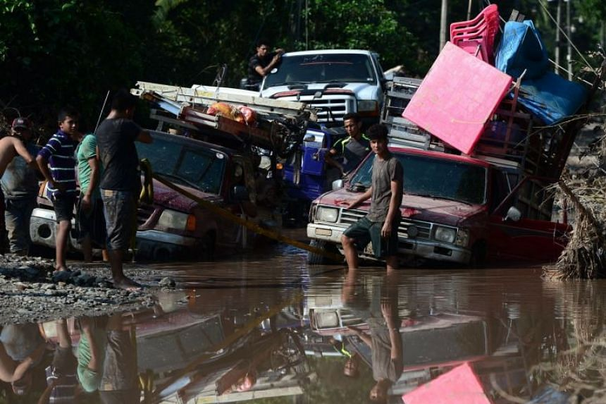 Workers of banana fields come across a flooded road while evacuating the area in El Progreso, Honduras, on Nov 14, 2020.