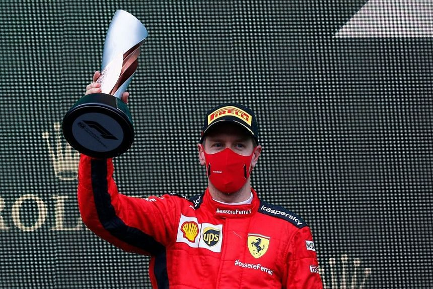 Ferrari's Sebastian Vettel celebrates on the podium with a trophy after finishing the race in third place on Nov 15.