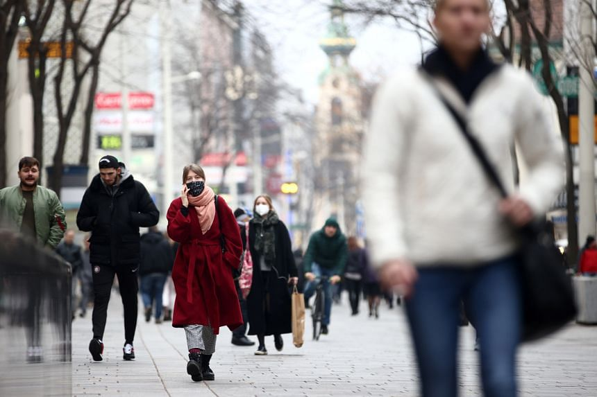 People walk down a shopping street in Vienna, on Nov 13, 2020.